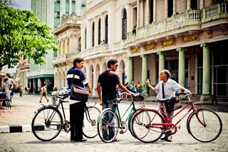 3 male cyclists talking on the road - Santa Clara, Cuba