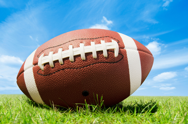 American football, resting in the green grass with a bright blue sky in the background.