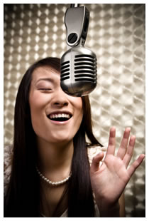 Asian woman singing in a recording booth