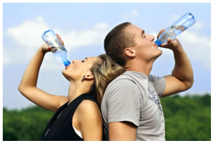 Athletic woman and man drinking bottled water
