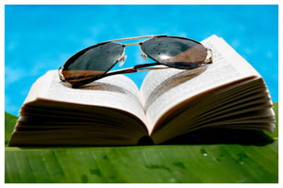 Book with sunglasses, palm leaf