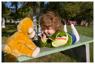 Boy on a picnic table talking to a stuffed monkey toy