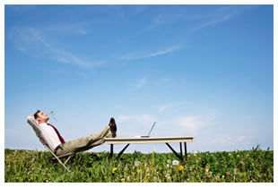 Businessman reclined on a Muskoka chair outside with laptop on a table