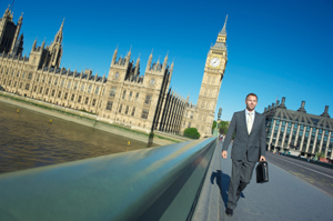 Businessman in a gray suit walking with his briefcase on a bridge near Big Ben in London, UK.