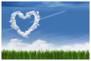 Cloud heart in a clear blue sky with vibrant green grass on the ground