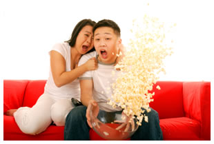 Scared couple spilling popcorn