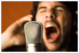 Dark haired man screaming into a microphone.  Focus is on the microphone.