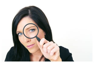 Dark haired woman holding a magnifying glass up to her left eye