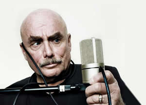 Don LaFontaine holding a microphone in his left hand, microphone cable draped over his left ear.
