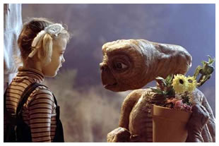 Drew Barrymore as a child actress in E.T. The Extra Terrestrial pictured with E.T. holding flowers.