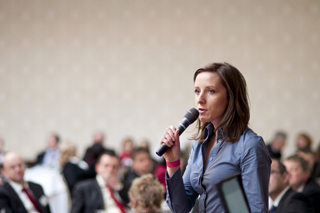 Female public speaker in a business conference setting. Holding a microphone.