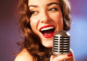Glamorous wavy haired brunette with bright eyes singing into a microphone