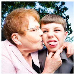 Grandma kissing her annoyed grandson's cheek