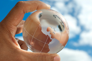Human hand holding a globe made of glass with frosting on where the continents are.
