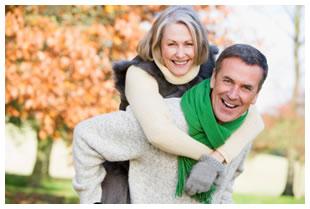 Senior man (husband) giving his wife a piggyback