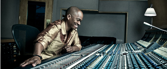 Jesse Campbell in studio sitting at a mixing board / control