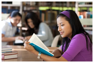 Latin American / Hispanic young woman reading a book in the library