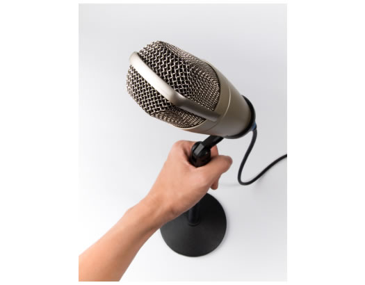 left hand holding vintage microphone