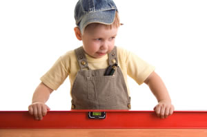Little boy with a cap on using a level (gauge)
