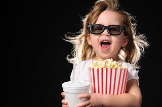 Little girl watching a movie in 3D, wearing black glasses and holding popcorn in a red and white container and a drink.