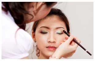 Asian woman getting makeup applied by a makeup artist