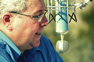 Male announcer, middle age, wearing blue shirt speaking into a suspended microphone.