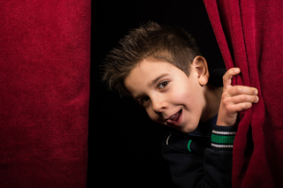 Young tween boy actor, smiling mischievously at the camera, standing between two red theatre curtains