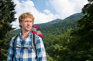 Young, fair-haired man in a plaid shirt wearing a backpack, hiking through the forest. Lots of green trees, mountain-like terrain and a bright blue sky.
