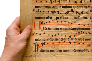 Male hand holding a piece of medieval/baroque music. Latin text penned beautifully in calligraphy.