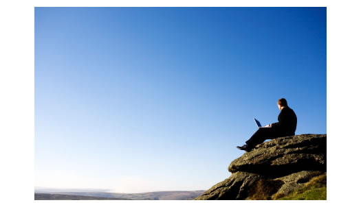 Man overlooking a cliff working on a laptop computer