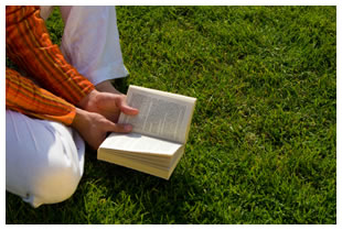 Man sitting in the grass reading a book