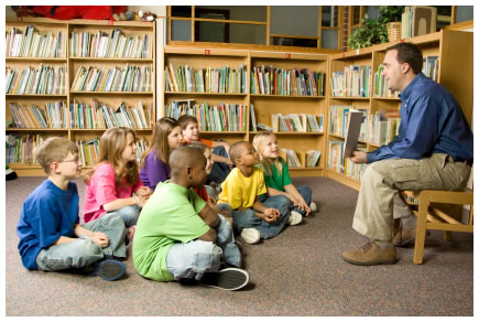 Male teacher reading to kids in a school library