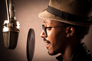 Man recording a voiceover; pop filter, microphone