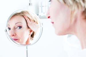 Mature woman looking at her face in a mirror, reflection