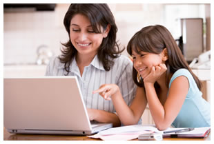 Mother working from home with youthful daughter looking on