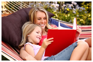 Mother reading to her young daughter while resting on a hammock