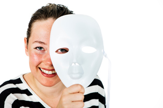 Older child actor holding a white theatre mask, smiling.