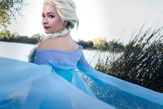 Queen Elsa from Frozen out in the open air, bright desolate area, looking back at the camera.