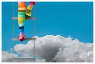 Rainbow stockings feet climbing ladder into the sky