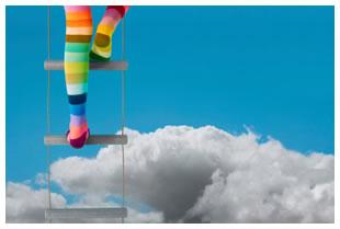 Rainbow stockings feet climbing ladder into the sky