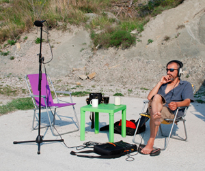 A sound engineer at work during on location sound recording Slovenia with a stereo microphone on a sandy beach with dunes.
