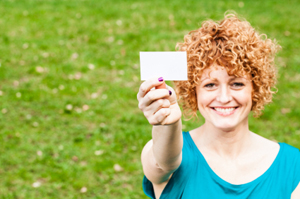 Red haired woman in a grassy field smiling at the camera while holding up a placeholder or blank business card suggesting her identity/name.  Her hair is short with tight springy curls. Blue shirt.
