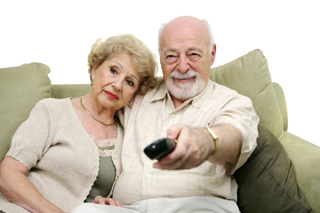Senior couple watching television. The wife is not enthralled but the husband is content with the programming. Husband is holding a remote control.
