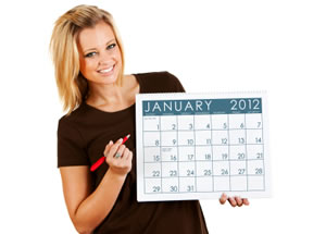 Smiling woman holding a January 2012 calendar