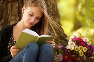 Teenage girl reading a book in the forest with a bouquet of brightly coloured flowers beside her.