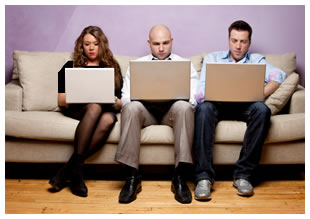 Three people sitting on a couch with laptops