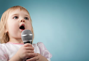 Female toddler singing into a microphone. Pink dress.