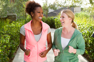 Two women jogging, talking and smiling as they jog down a paved path lined with green shrubbery.