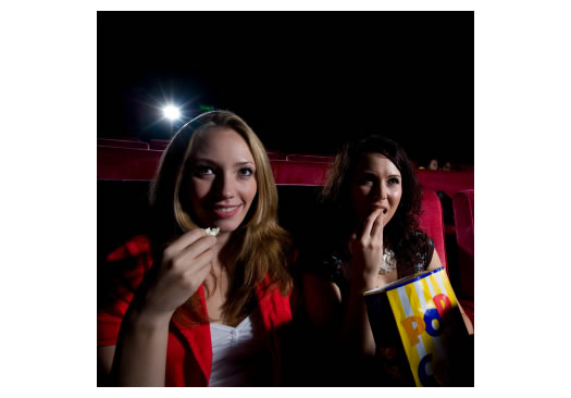 Two women watching a movie in the theatre