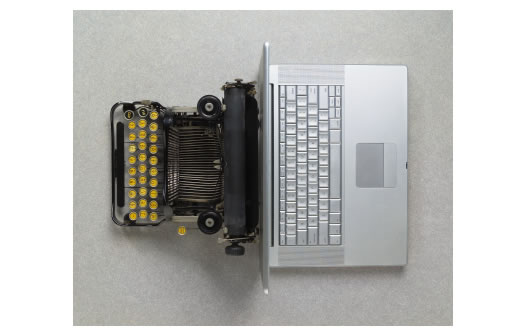 Typewriter back to back with a laptop